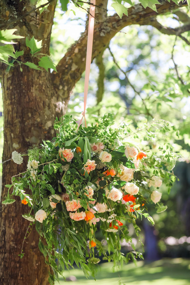 Hanging floral chandelier // Whimsical Garden Wedding flowers in Peach, green and silver Grey // Nikki Meyer Photography