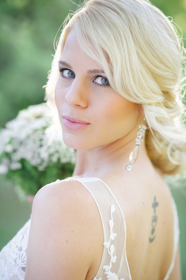 A deep V style Lace back wedding dress shows off tattoo. Lovely Rustic Garden Picnic Wedding // Nikki Meyer Photography