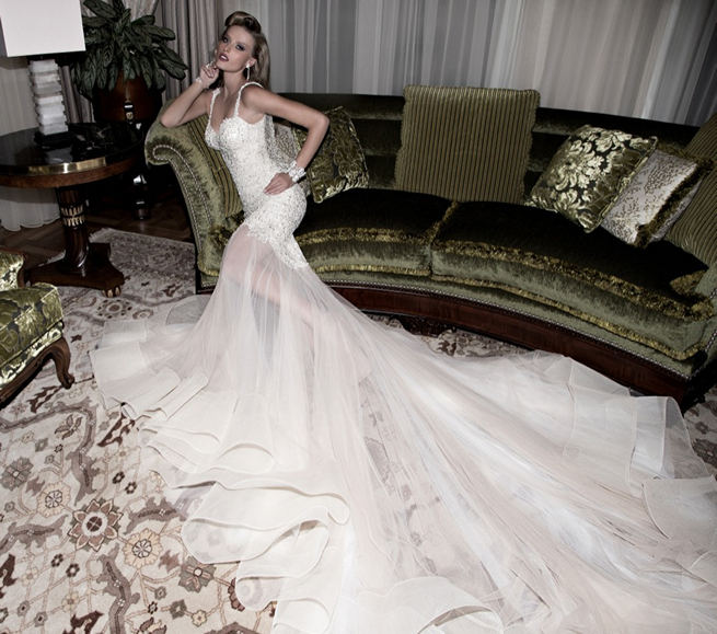 Galia Lahav's 2015 Lana bridal gown is blush colored with sheer panelling. The top of the gown is entirely embroidered in ivory crochet with sandstone pearls and sequins. The back of the gown has a very deep low cut and has a nude illusion with an embroidered drape sash. The skirt is a melange of ivory and dusted rose tulle.