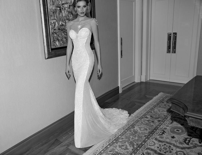 Galia Lahav's Joyce wedding dress from the 2015 Tales of the Jazz Age collection is a strapless and sheer sided art deco dress with a bejeweled top. The net fabric is fully embroidered with structural art deco motifs. The dress is finely cut with glistening sides and iridescent irregular faceted stones. The gown comes complete with a removable bejeweled necklace made of metallic mesh and crystal beaded rhodium strands.