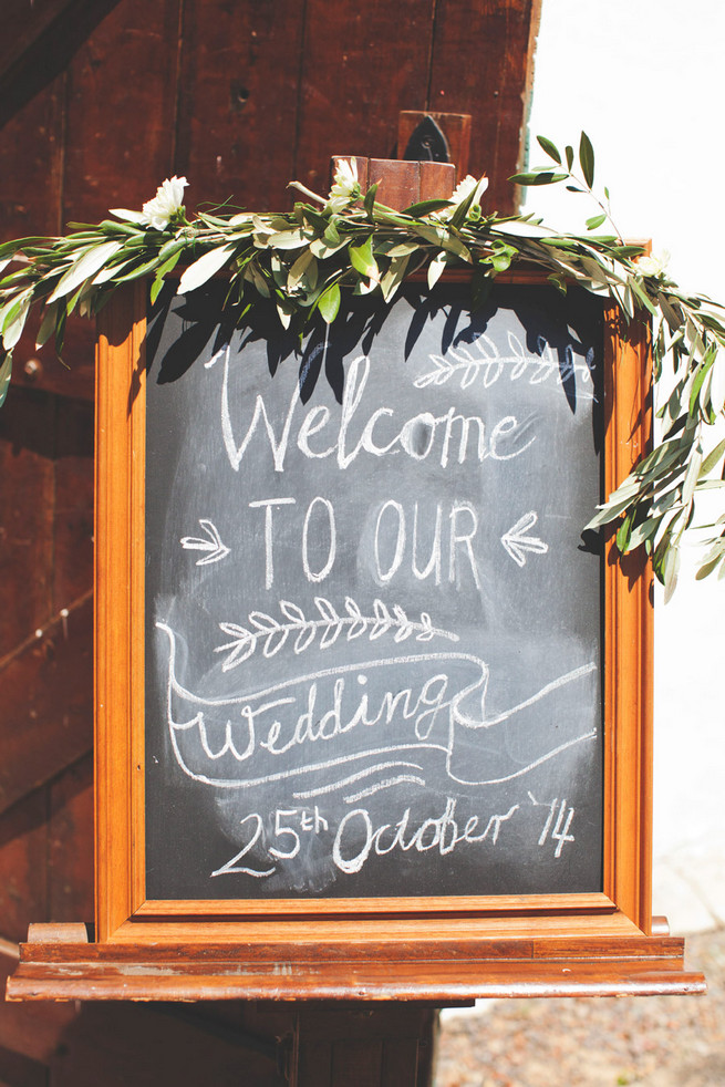 Welcome to our wedding chalkboard sign with laurel wreath. Groom in grey suit with grey tie. Green White Rustic South African Wedding // Justin Davis Photography