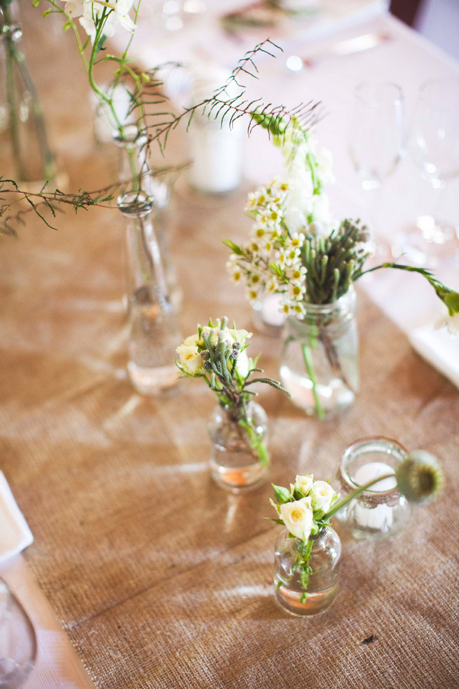 Burlap table runner. Single stem greens in mix and match bottles. Wedding reception decor. Green White Rustic South African Wedding // Justin Davis Photography
