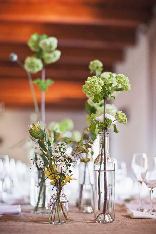 Single stem greens in mix and match bottles. Wedding reception decor. Green White Rustic South African Wedding // Justin Davis Photography