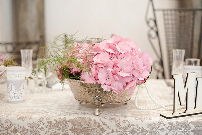 Romantic floral arrangement: silver urn with pink hydrangea and leather leaf ferns place on bridal table.