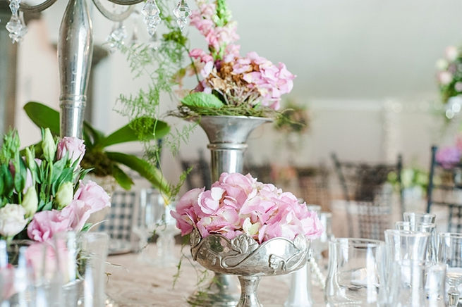 Blush and pink wedding flowers in silver urns and vases on wedding reception tables: hydrangea, roses, lisanthius and leatherleaf ferns // D'amor Photography