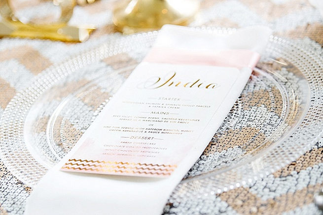 Gold embossed script style menu, clear beaded underplate with white and gold glitter chevron table linen