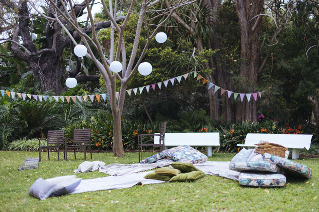 Bunting, paper lanterns and Wedding picnic area with blankets and cushions // Succulent Garden Wedding // Claire Thomson Photography