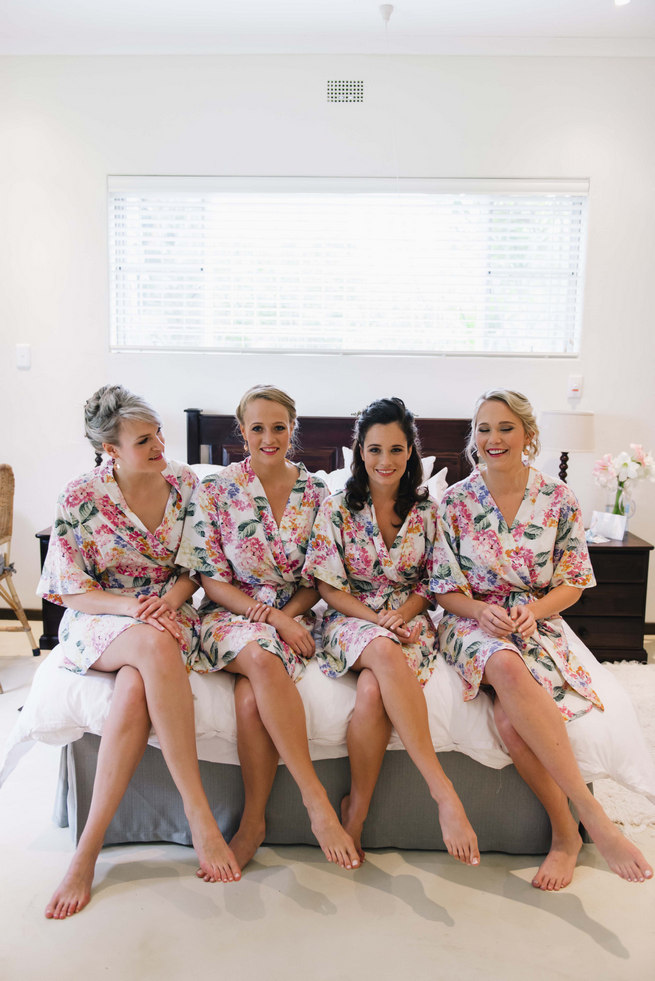 Bridesmaids getting dressed in matching floral print robes // Succulent Garden Wedding // Claire Thomson Photography