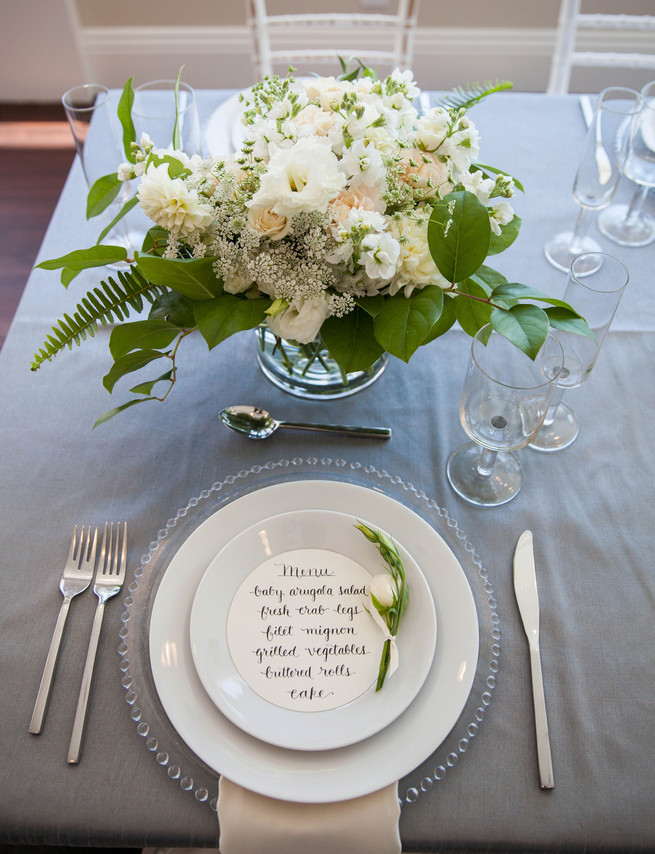 Hand calligraphed menu by Steele My Hear, place setting on clear glass charger and elegant fresh florals by Angel's Petals. Elegant Gray Blue Nautical Wedding by Rachel Capil Photography and Lindsay Lauren Events
