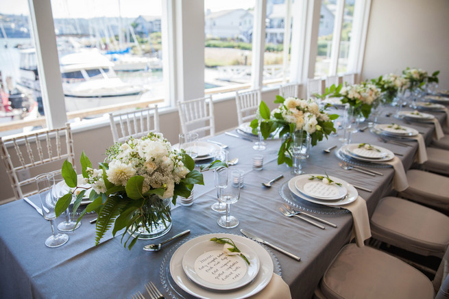 Grey and white tablescape using place settings on clear glass chargers, linens by Napa Valley Linens and elegant fresh florals by Angel's Petals. Elegant Gray Blue Nautical Wedding by Rachel Capil Photography and Lindsay Lauren Events