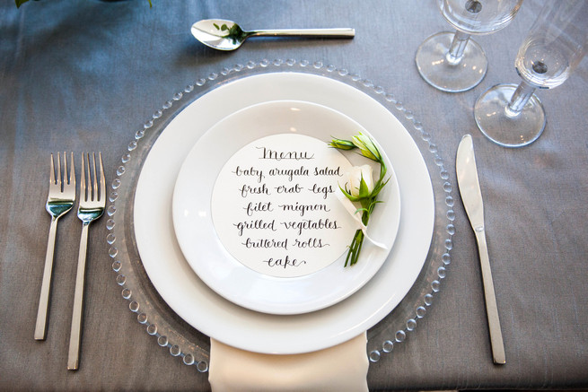 Hand calligraphed menu by Steele My Heart place setting on clear glass charger. Elegant Gray Blue Nautical Wedding by Rachel Capil Photography and Lindsay Lauren Events