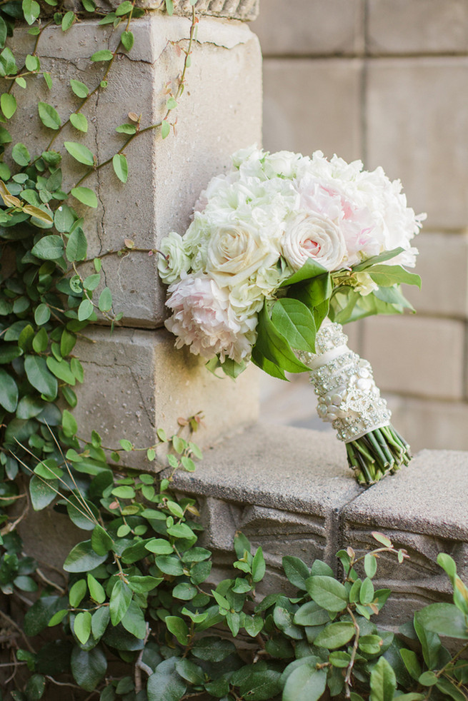 All white wedding bouquet of white roses, white hydrangea, white peony and pale blush roses.