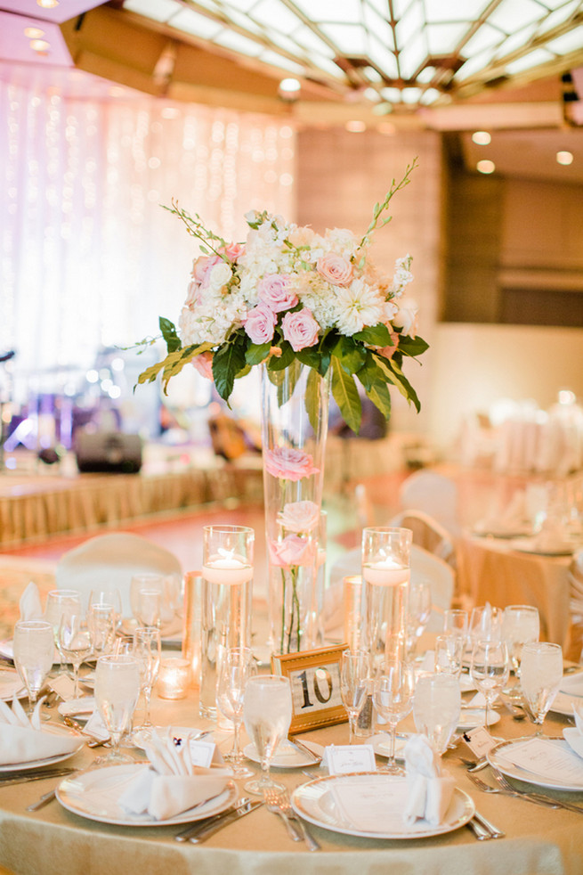 Chic Wedding reception florals of white hydrangea, blush roses, white roses and green fillers with white blossoms.