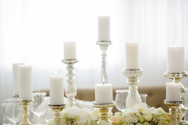 Gorgeous pillar candles. Super chic sweetheart table! White on White Glamorous Wedding Ideas by ENV Photography. Styled by Elegant Touches and Atmosphere Weddings