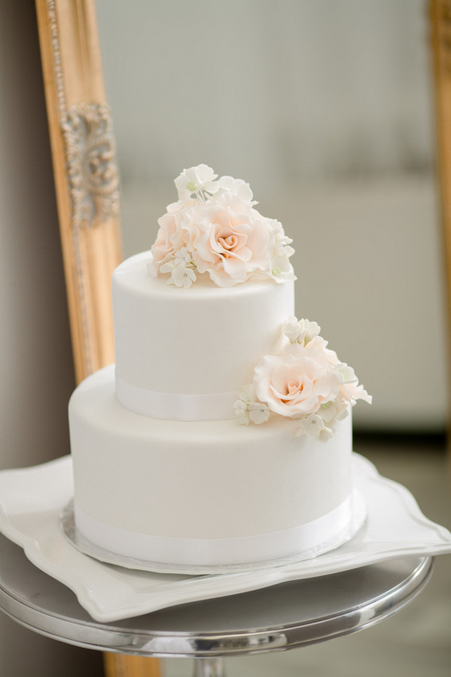 Stunning white cake with flower topper and detail. White on White Glamorous Wedding Ideas by ENV Photography. Cake by The Art of Cake.