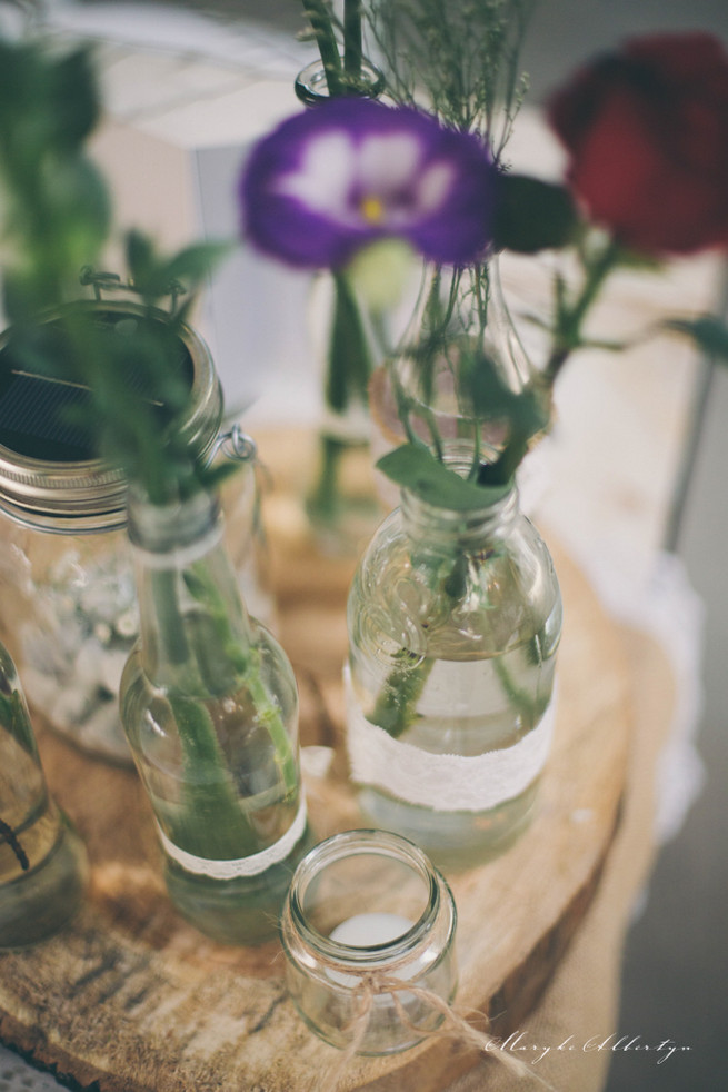 Rustic table decor with wood slabs, vintage bottles, lace and single stem roses.