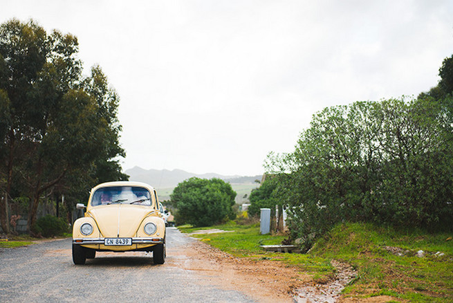 Bride arriving in vintage Volkswagen Beetle. Woodlands Winter Wedding in deep blue, burgundy and emerald green // Knit Together Photography