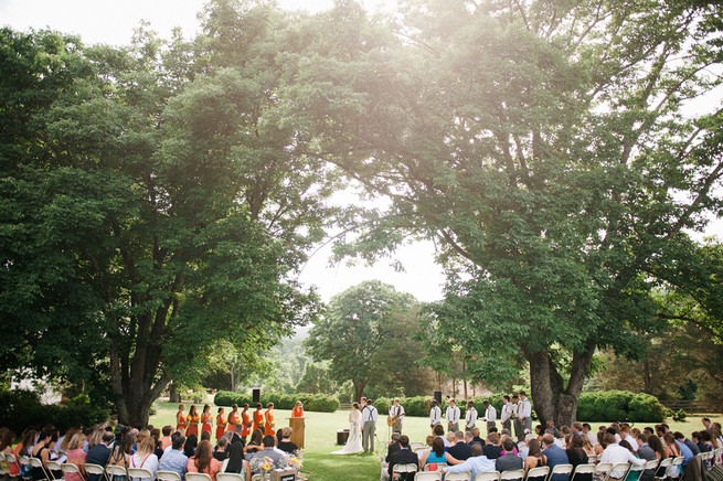 Outdoor wedding ceremony under trees.  Coral Navy Mustard Wedding / Meredith McKee Photography