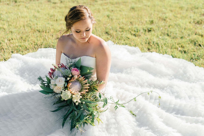 Bride with protea cascade bouquet / Langkloof Roses Wedding, Cape Town - Claire Thomson Photography