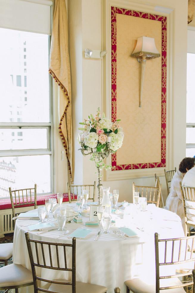 White hydrangea, cream and blush roses, white lillies, ivy wedding floral centerpiece