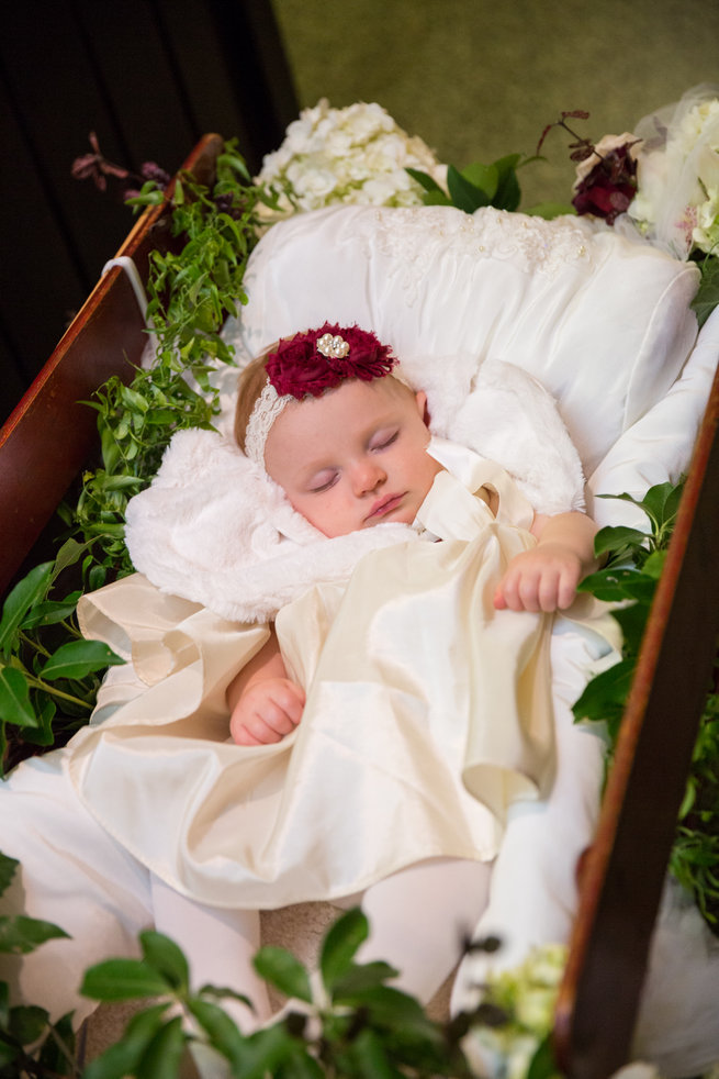 Flower girl sleeping in floral cart - Beautiful Burgundy and Tan Wedding - Molinski Photo