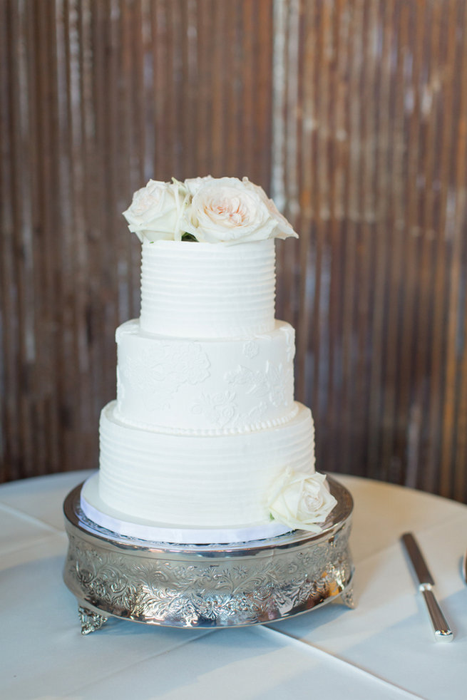 All white wedding cake with fresh flowers. Modern Urban Wedding at Old Cigar Warehouse / Ryan and Alyssa Photography