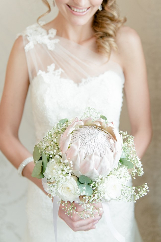 Breathtaking Wedding Bouquet Recipe: Simple but striking - a large blush pink King Protea surrounded by delicate babys breath, eucalyptus and white roses. Click to blog for more gorgeous bouquet ideas.