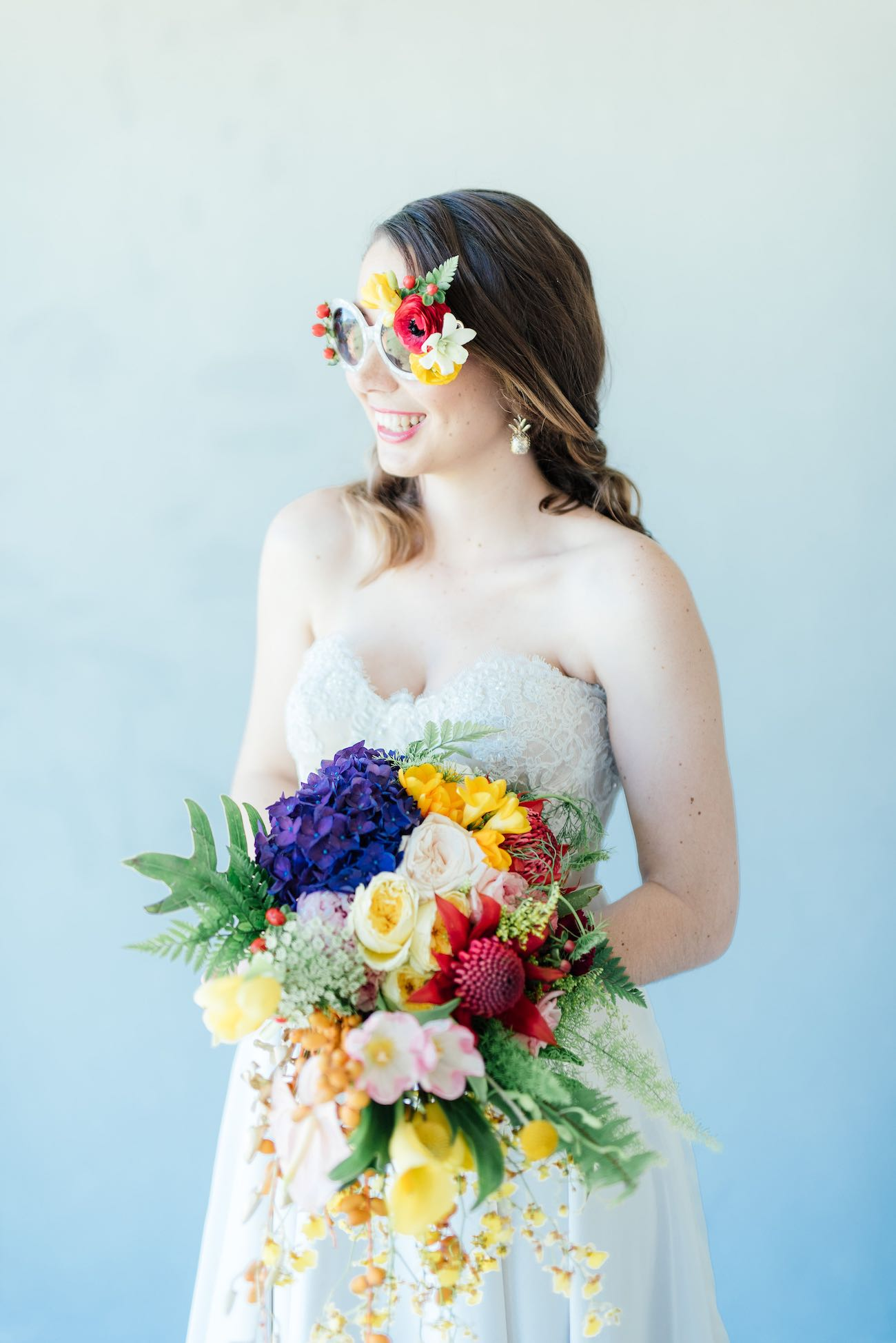 "STUNNING tropical wedding bouquet made from a cascade of bright blue hydrangea, yellow lilies, ferns, tulips. roses, queen annes lace, billies balls, protea and beautiful blooms! Super cute ""tutti frutti"", Carmen Miranda style tropical flower crown for a tropical bride in bright colors. Fun and cute. Tropical Wedding Ideas photographed by Debbie Lourens Photography"