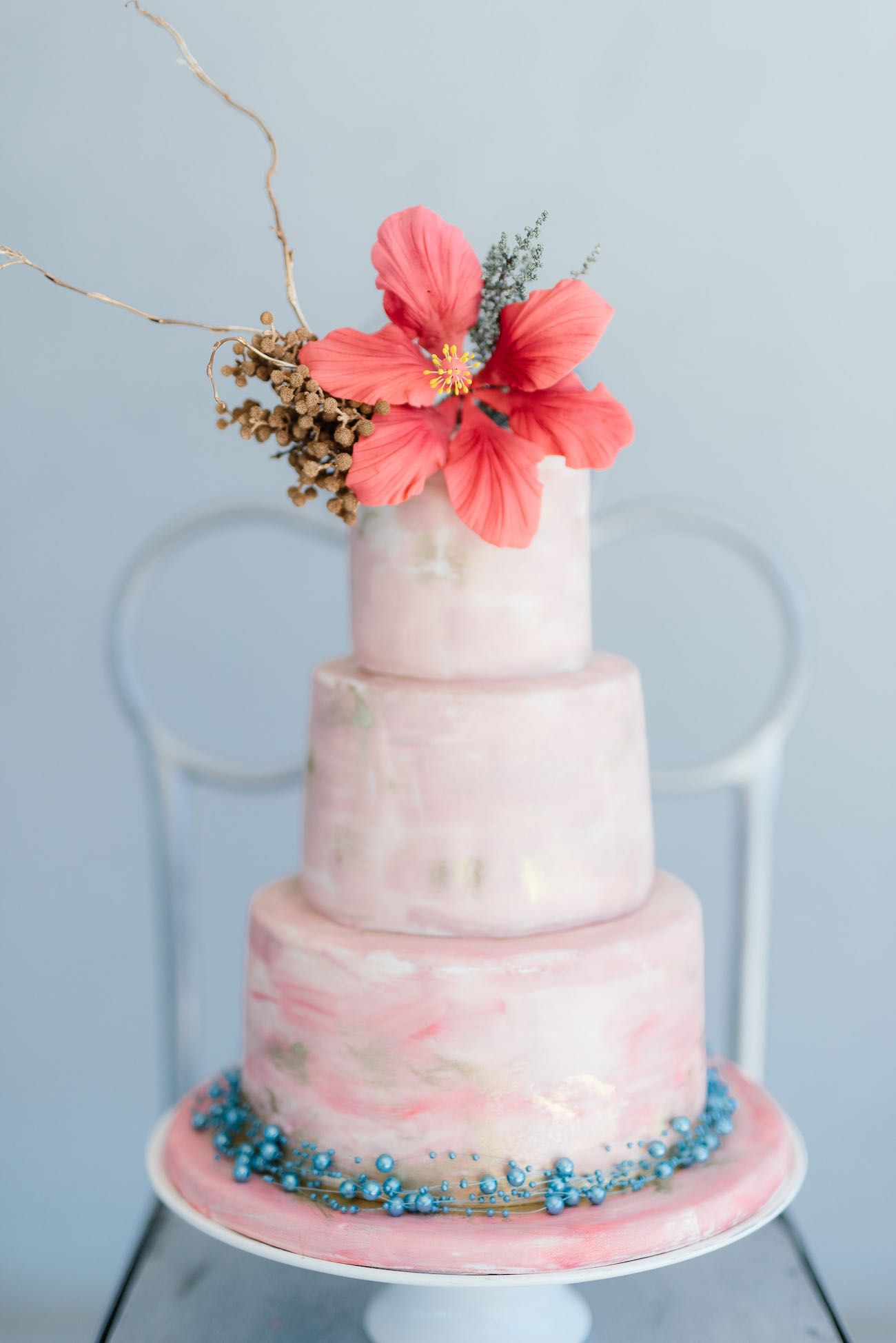 Soft pink tropical wedding cake with touches of gold and a hibiscus flower topper. Hand painted, watercolor. Click for the most absolutely gorgeous Tropical Wedding ideas ever!
